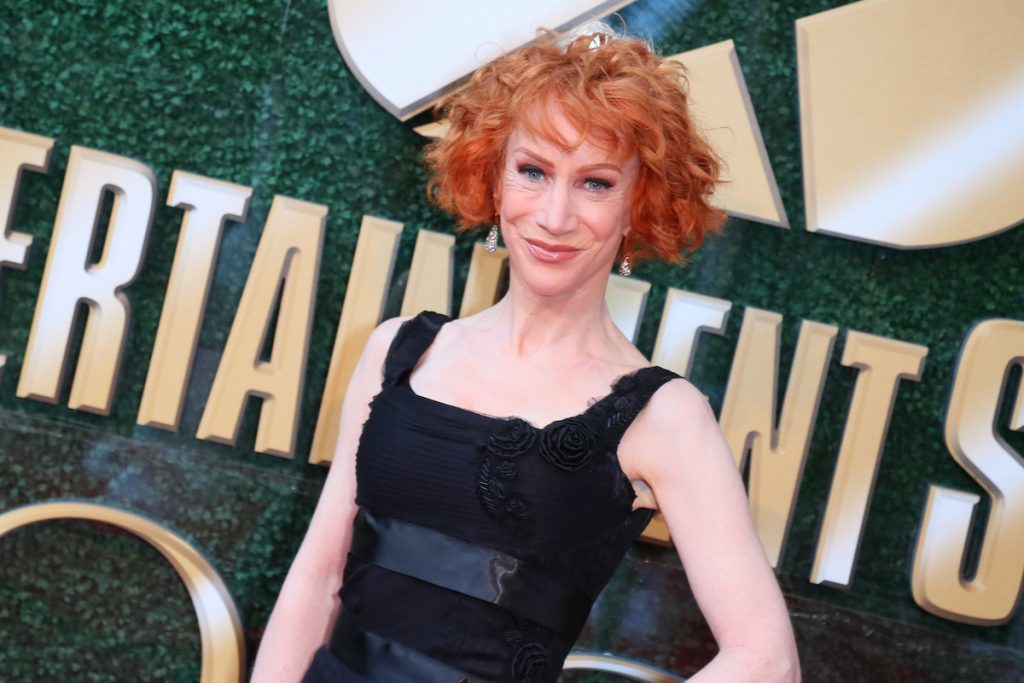 Kathy Griffin smiling in front of a green and gold background