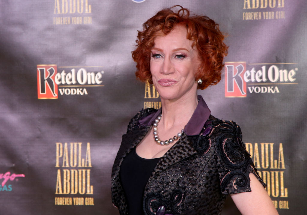 Kathy Griffin smiling in front of a dark background
