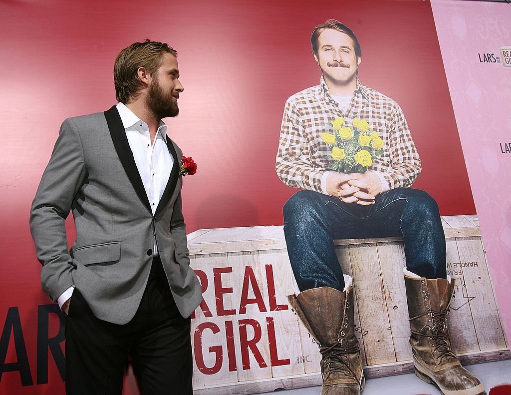 Ryan Gosling turned to the side, looking at a photo of his character from 'Lars and the Real Girl'