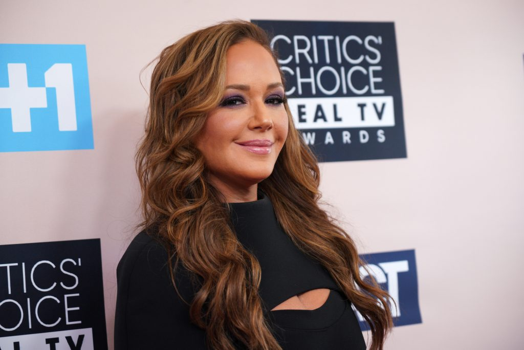 Leah Remini smiling in front of a white background with logos