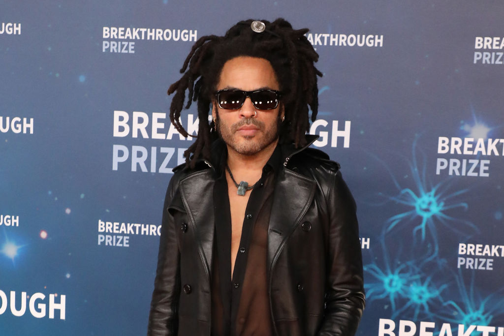 Lenny Kravitz standing in front of a blue background, wearing sunglasses