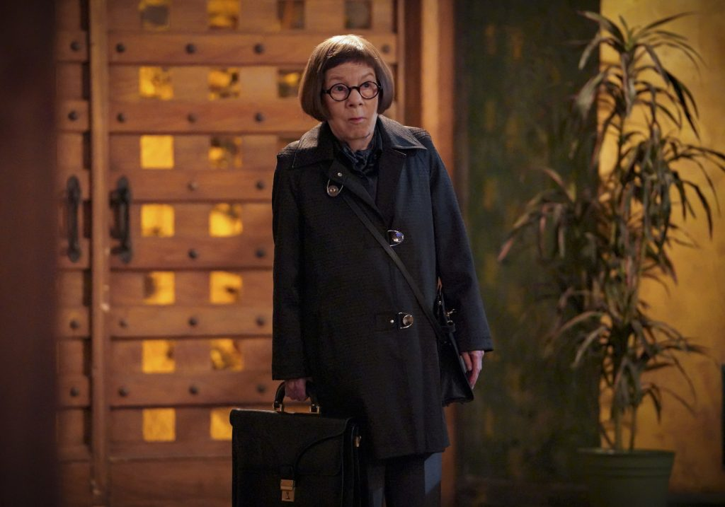 Linda Hunt as Hetty Lange, holding a briefcase standing in front of a set of doors