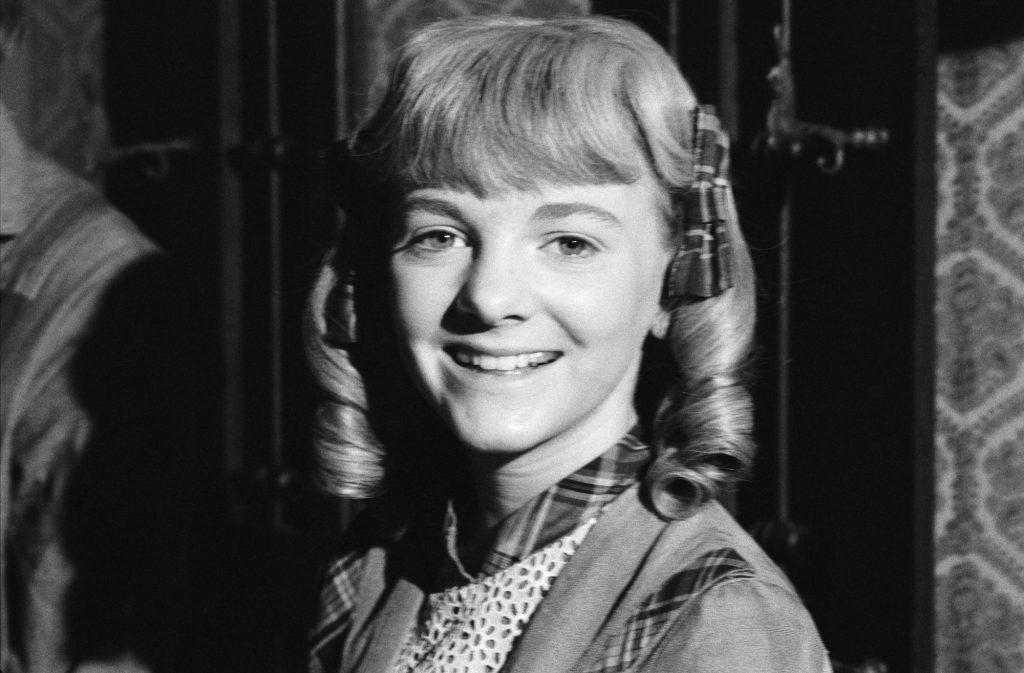 (L-R) Alison Arngrim as Nellie Oleson smiling, in black and white