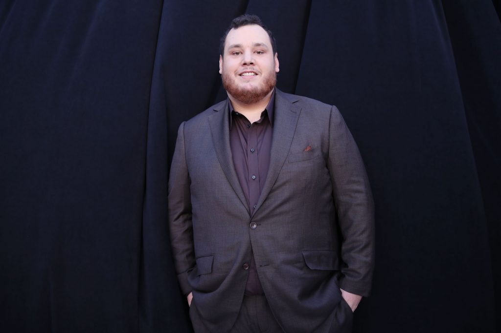 Luke Combs smiling in front of a black background