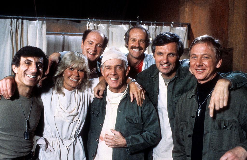 (L-R) Jamie Farr, Loretta Swit, David Ogden Stiers, Harry Morgan, Mike Farrell, Alan Alda, and William Christopher smiling