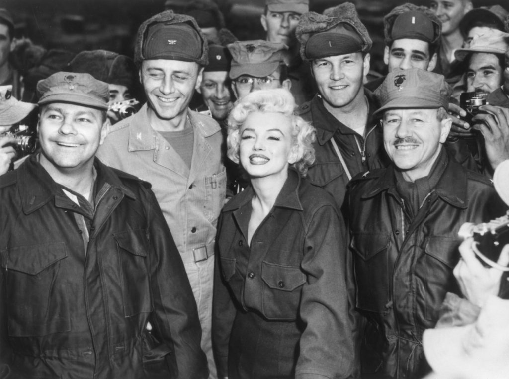 Marilyn Monroe poses for a photo with U.S. soldiers