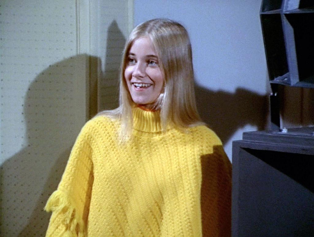 Maureen McCormick as Marcia Brady smiling, wearing a yellow sweater
