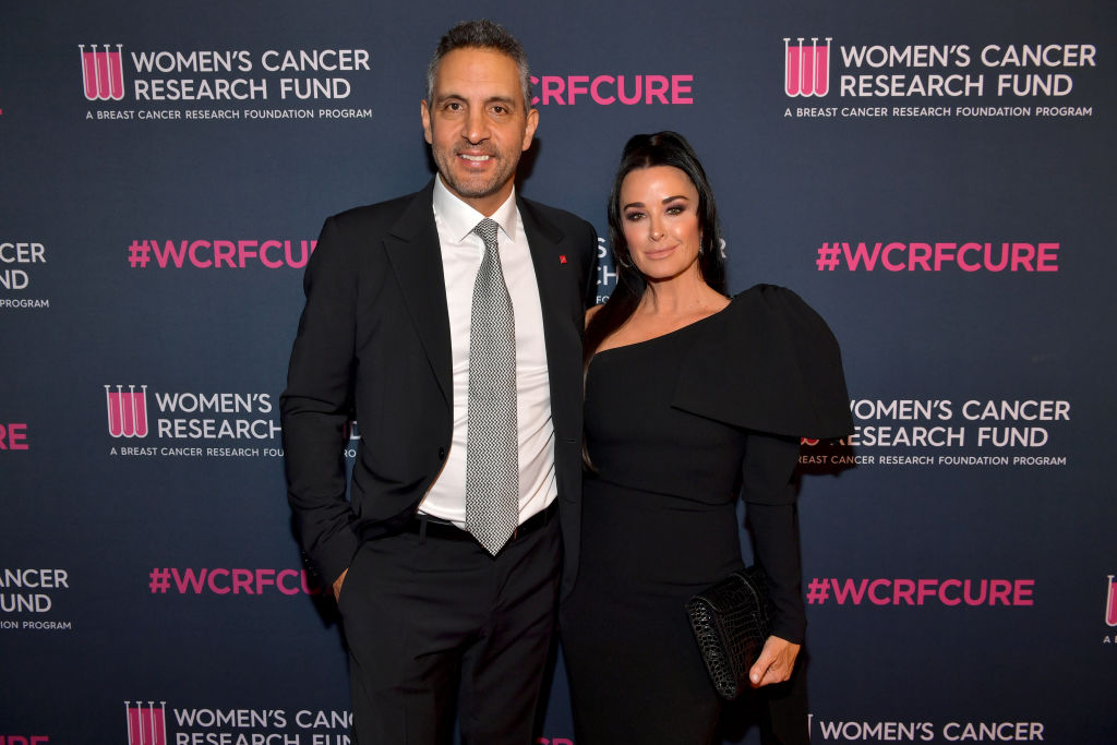 (L-R) Mauricio Umansky and Kyle Richards smiling in front of a dark background with pink logos