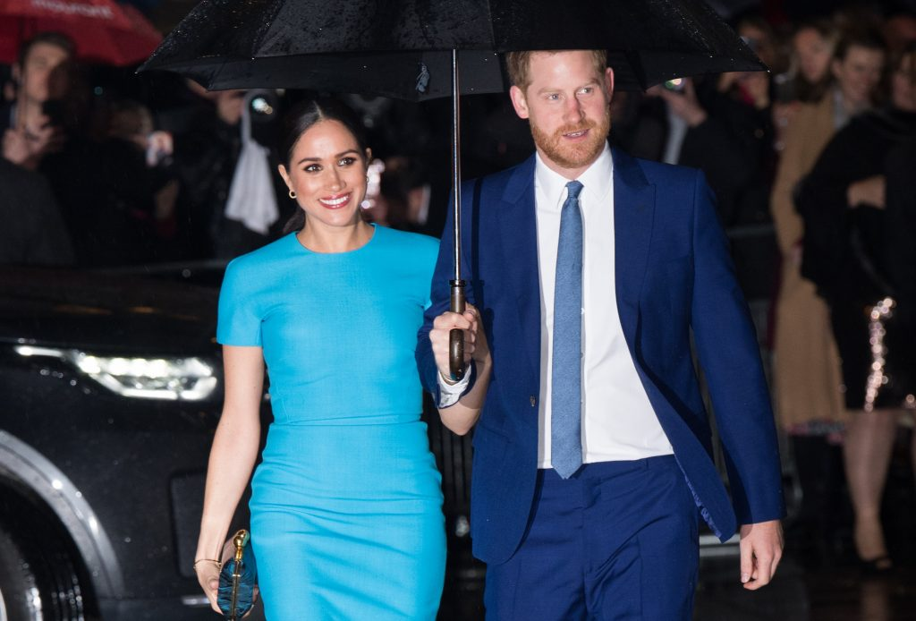 Meghan Markle and Prince Harry smiling, walking under and umbrella