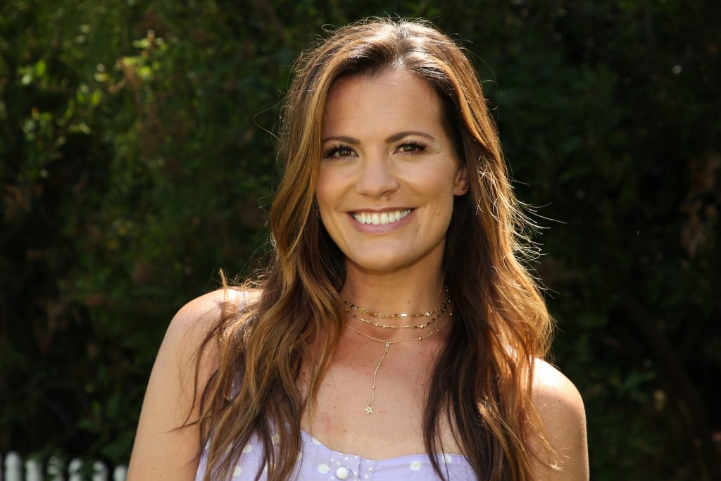 Melissa Claire Egan smiling in front of a bush