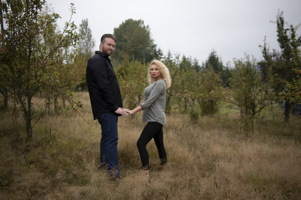 90 Day Fiancé couple Mike and Natalie hold hands facing one another in a field.