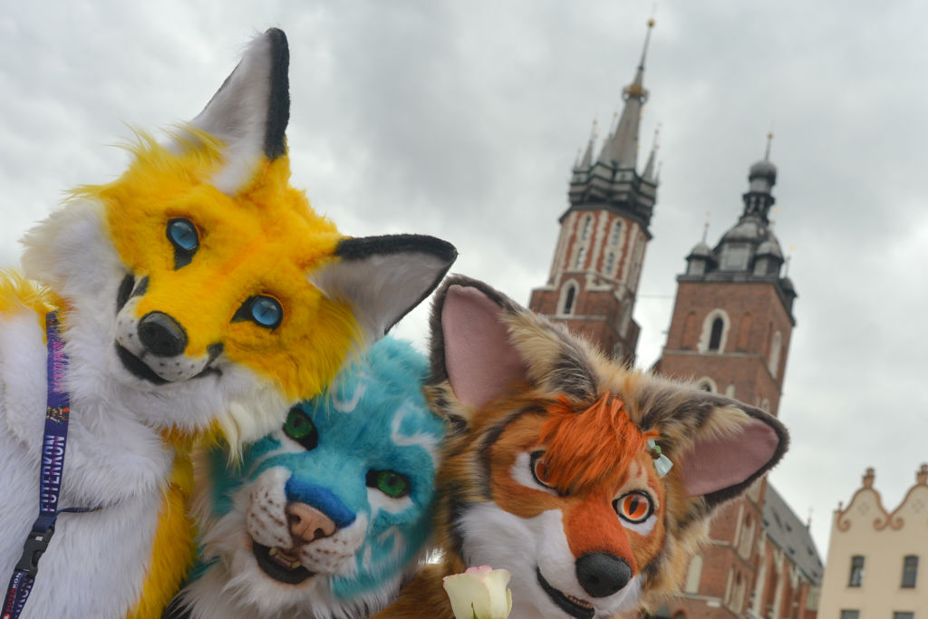 Members of different Furry Fandom Conventions pose for a photo at Adam Mickiewicz's monument in Krakow Main Market Square