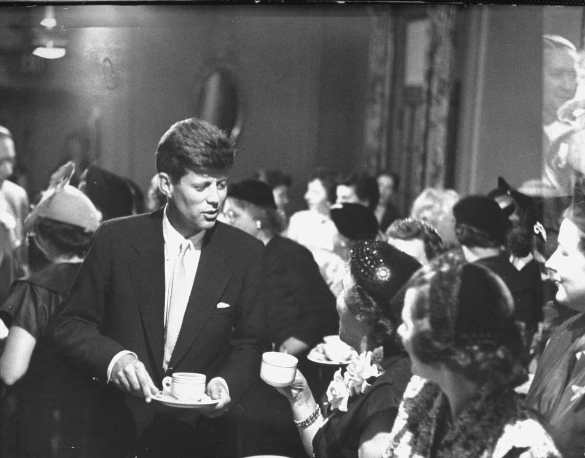 John Kennedy chatting with women at a political tea during his campaign