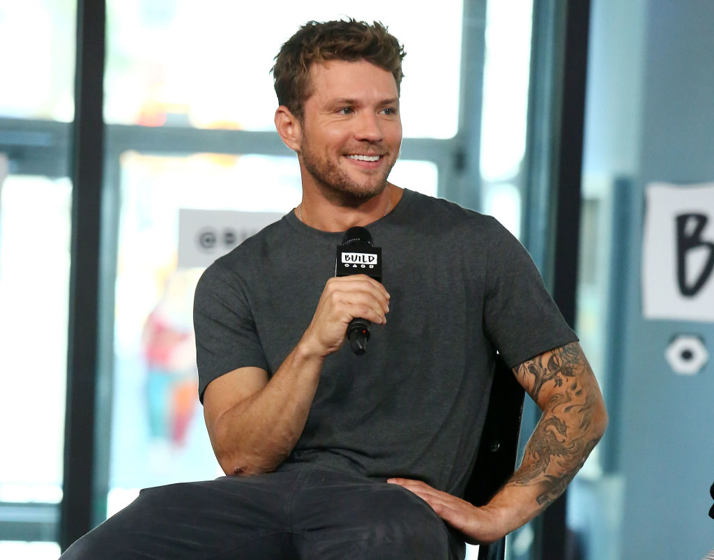 Ryan Phillippe smiling, holding a microphone