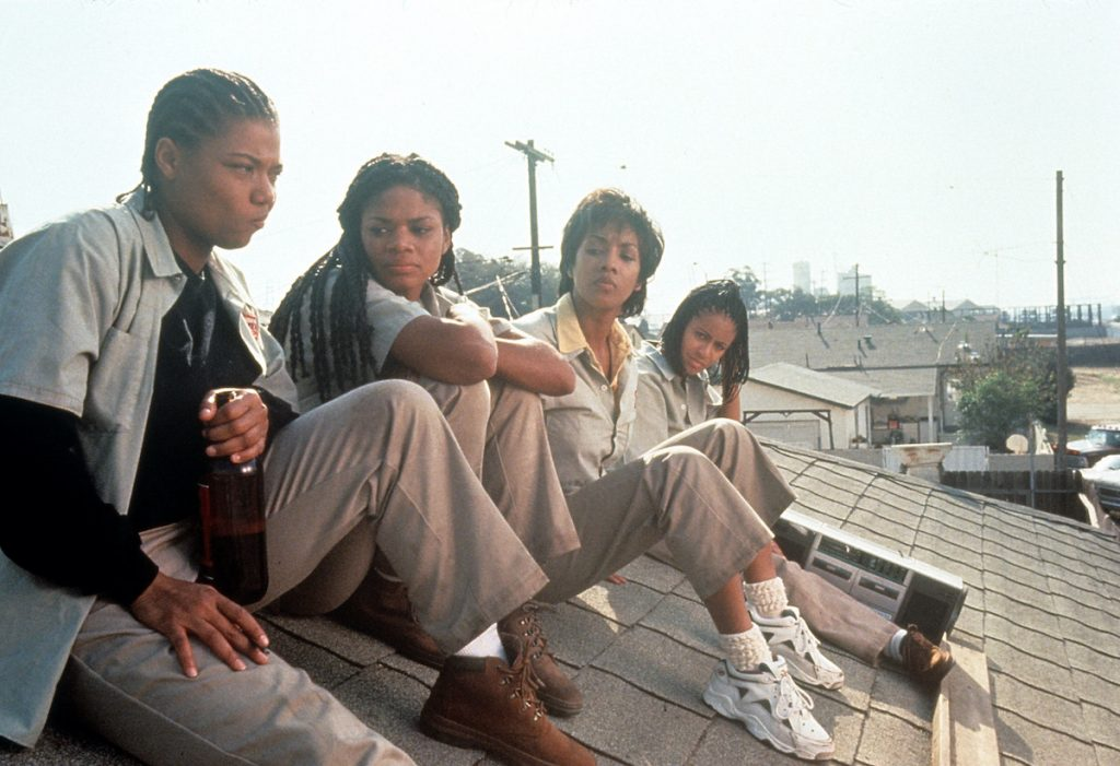 Queen Latifah, Kimberly Elise, Vivica Fox and Jada Pinkett all sitting on the roof of a house in a scene from the film 'Set It Off', 1996
