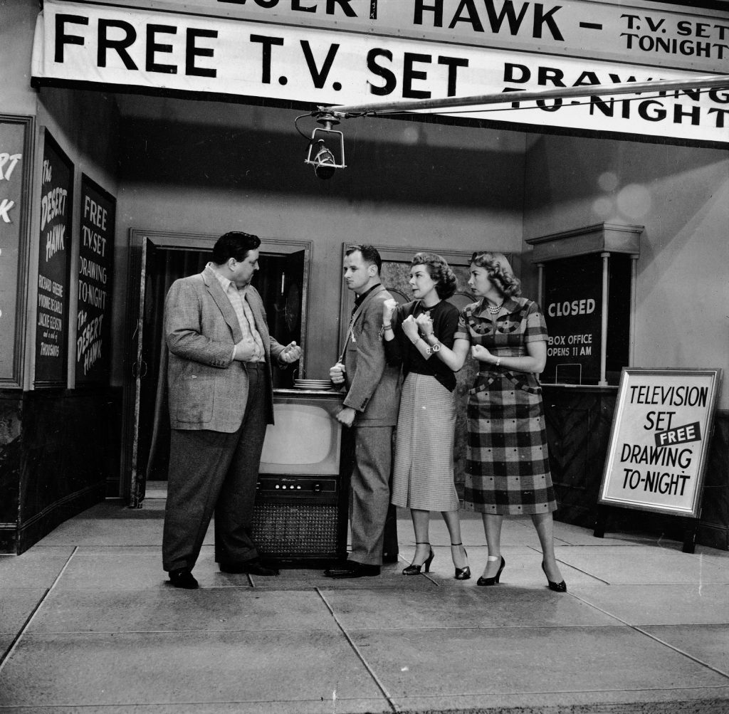 Jackie Gleason, Art Carney, Joyce Randoph and Audrey Meadows stand by a banner announcing a raffle for a new TV on the set of 'The Honeymooners'