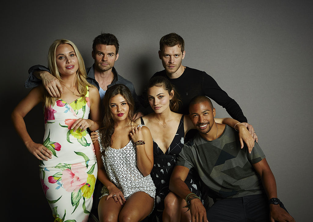 (L-R) Leah Pipes, Daniel Gillies, Danielle Campbell, Phoebe Tonkin, Joseph Morgan, and Charles Michael Davis smiling in front of a gray background