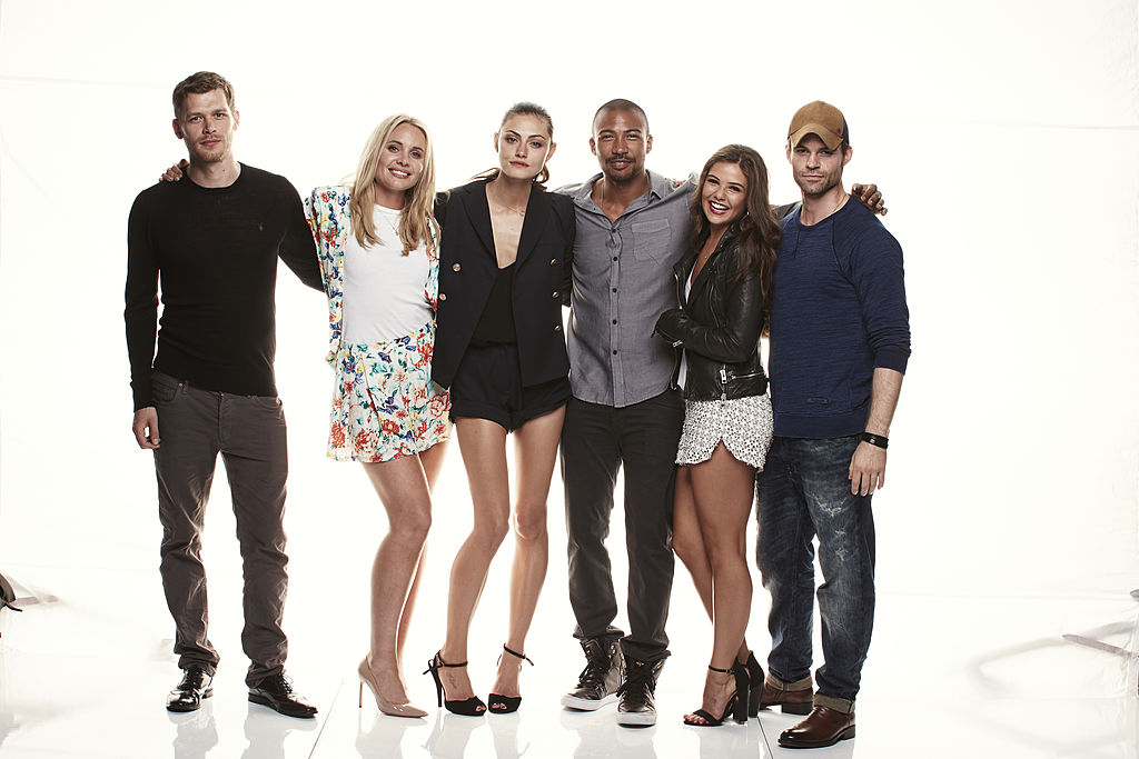 (L-R) Joseph Morgan, Leah Pipes, Phoebe Tonkin, Charles Michael Davis, Danielle Campbell, and Daniel Gillies smiling, standing in front of a white background