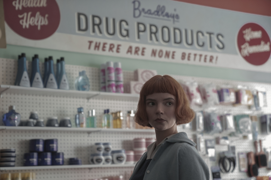 Anya Taylor-Joy stands in a pharmacy as Beth Harmon on 'The Queen's Gambit'
