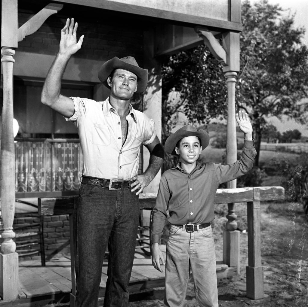 (L-R) Chuck Connors as Lucas McCain and Johnny Crawford as Mark McCain smiling and waving