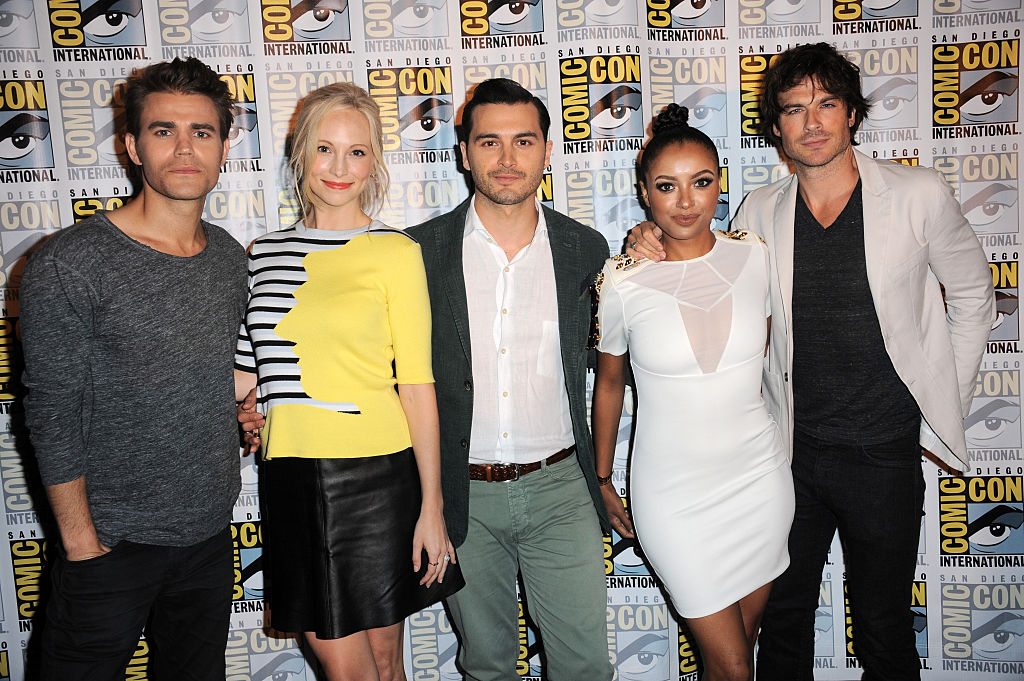 (L-R) Paul Wesley, Candice Accola, Michael Malarkey, Kat Graham and Ian Somerhalder smiling in front of a repeating background with the Comic Con logo
