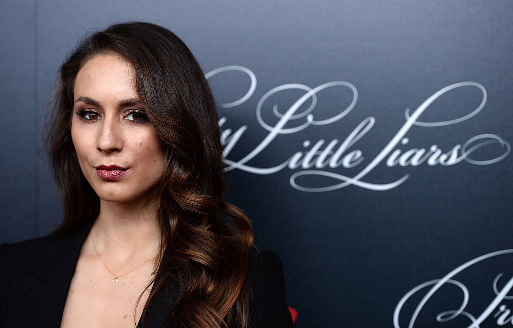 Troian Bellisario slightly smiling in front of a black background with Pretty Little Liars logo