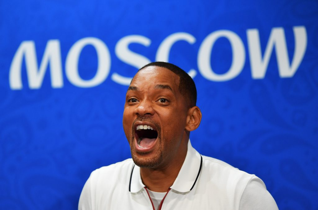 Will Smith with his jaw dropped, looking surprised, in front of a blue background