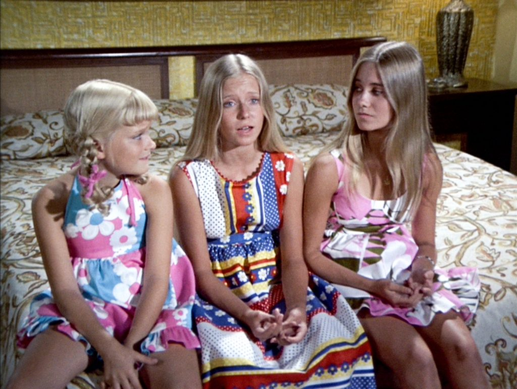 Susan Olsen, Eve Plumb, and Maureen McCormick on a bed in a scene from The Brady Bunch