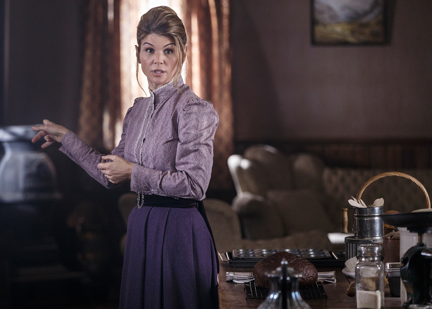 Lori Loughlin, in a purple blouse and skirt, shooting a scene for When Calls the Heart