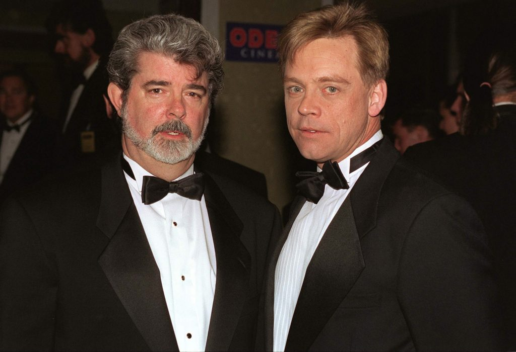 George Lucas and Mark Hamill wearing suits