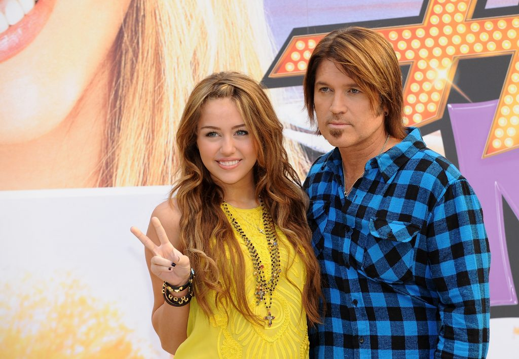 Miley Cyrus and Billy Ray Cyrus in front of a Hannah Montana poster