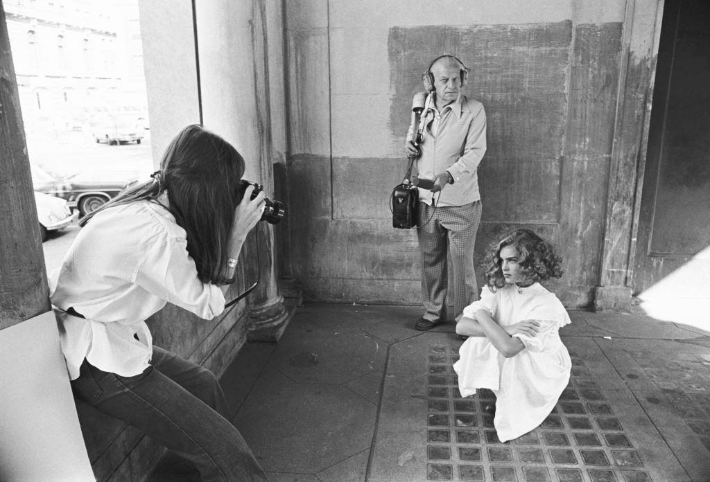 Brooke Shields near someone with a camera on the set of Pretty Baby