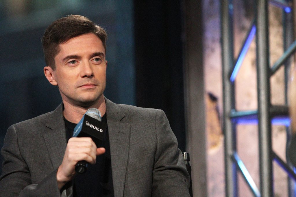 Topher Grace in front of a wall