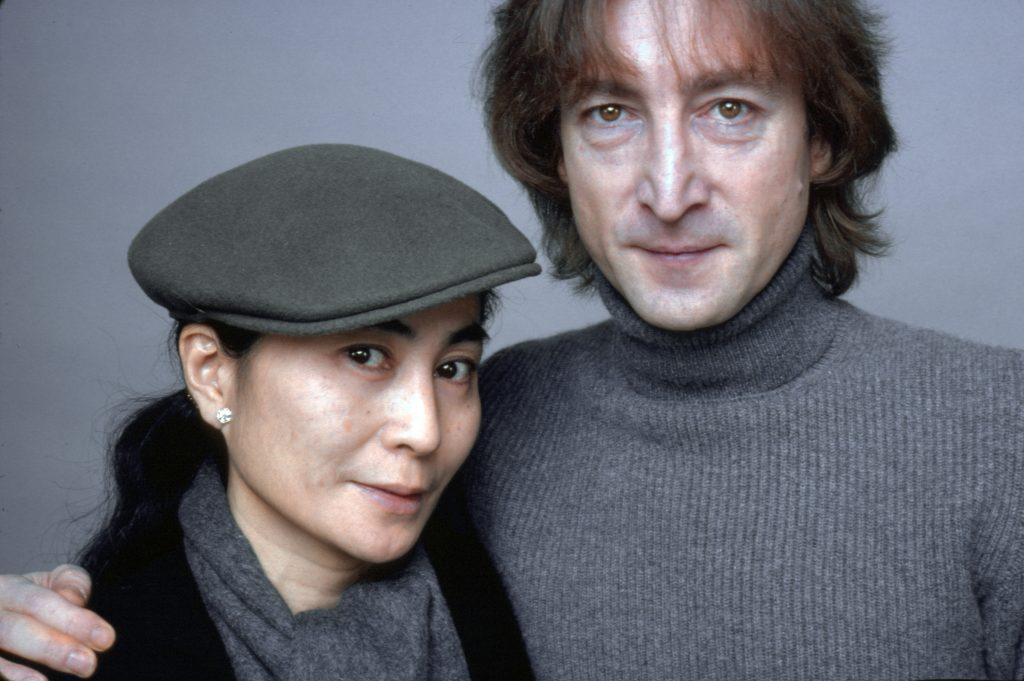 Yoko Ono wearing a beret and standing next to John Lennon