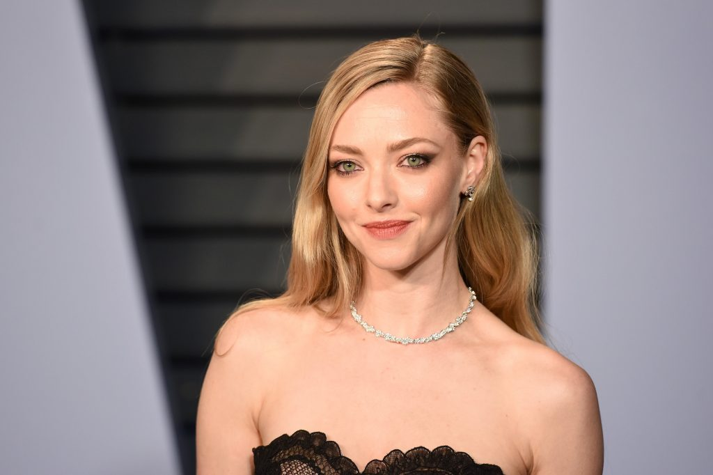 Amanda Seyfried smiling in front of a gray background