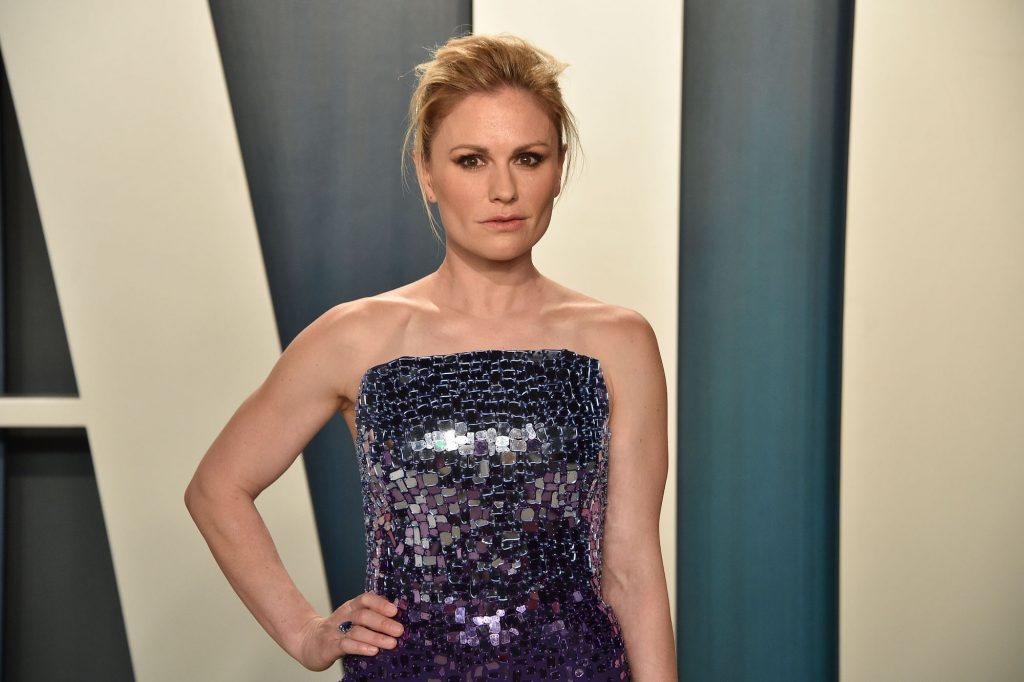 Anna Paquin smiling slightly in front of a blue background