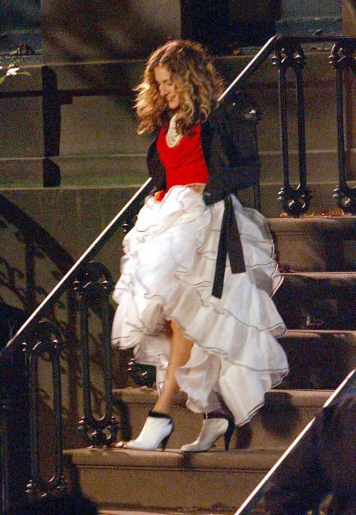 Sarah Jessica Parker as Carrie Bradshaw walks down the steps of her apartment