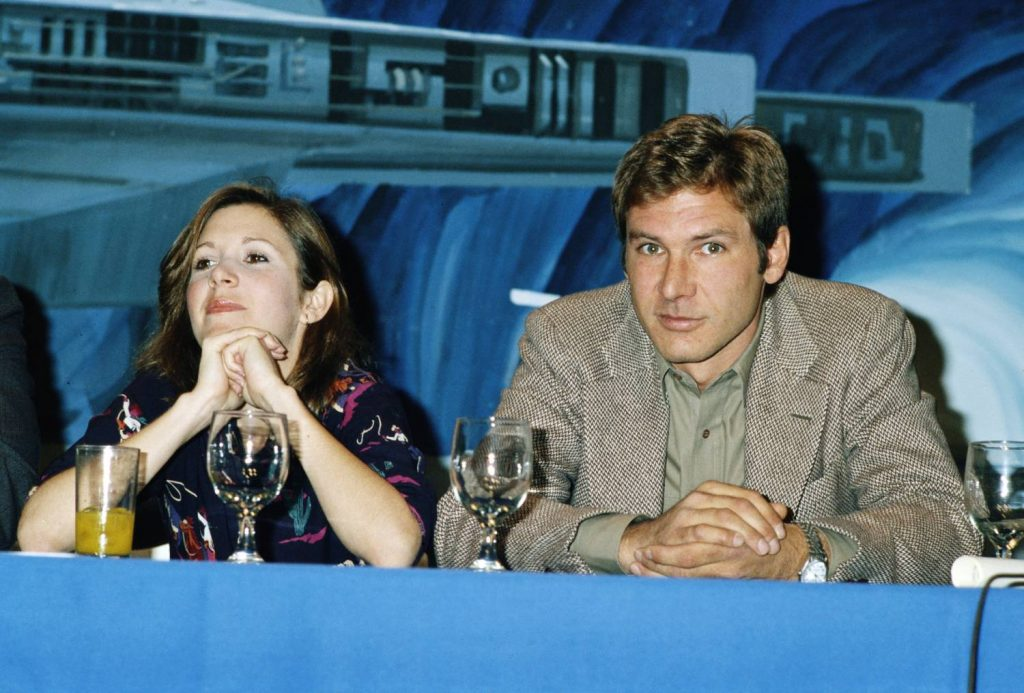 American actors Carrie Fisher and Harrison Ford at a press conference for one of the 'Star Wars' films, circa 1980.
