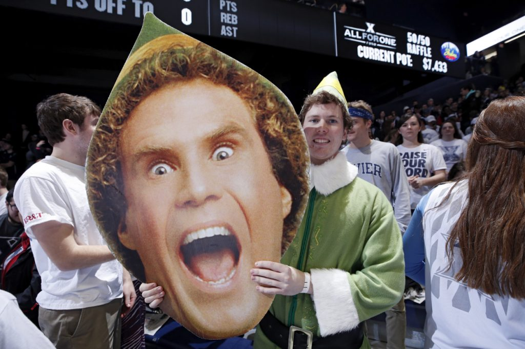 A basketball fan holds a cutout of actor Will Ferrell as Buddy the Elf before a game