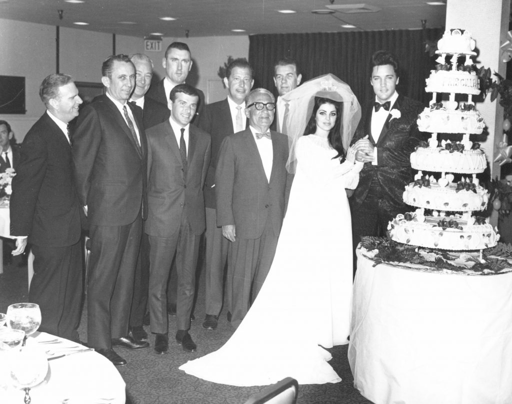 Elvis and Priscilla Presley near a cake