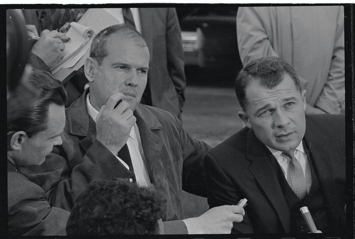 Dr. Samuel Sheppard listens as his attorney, F. Lee Bailey, answers news men's questions outside the home of Sheppard's brother Richard