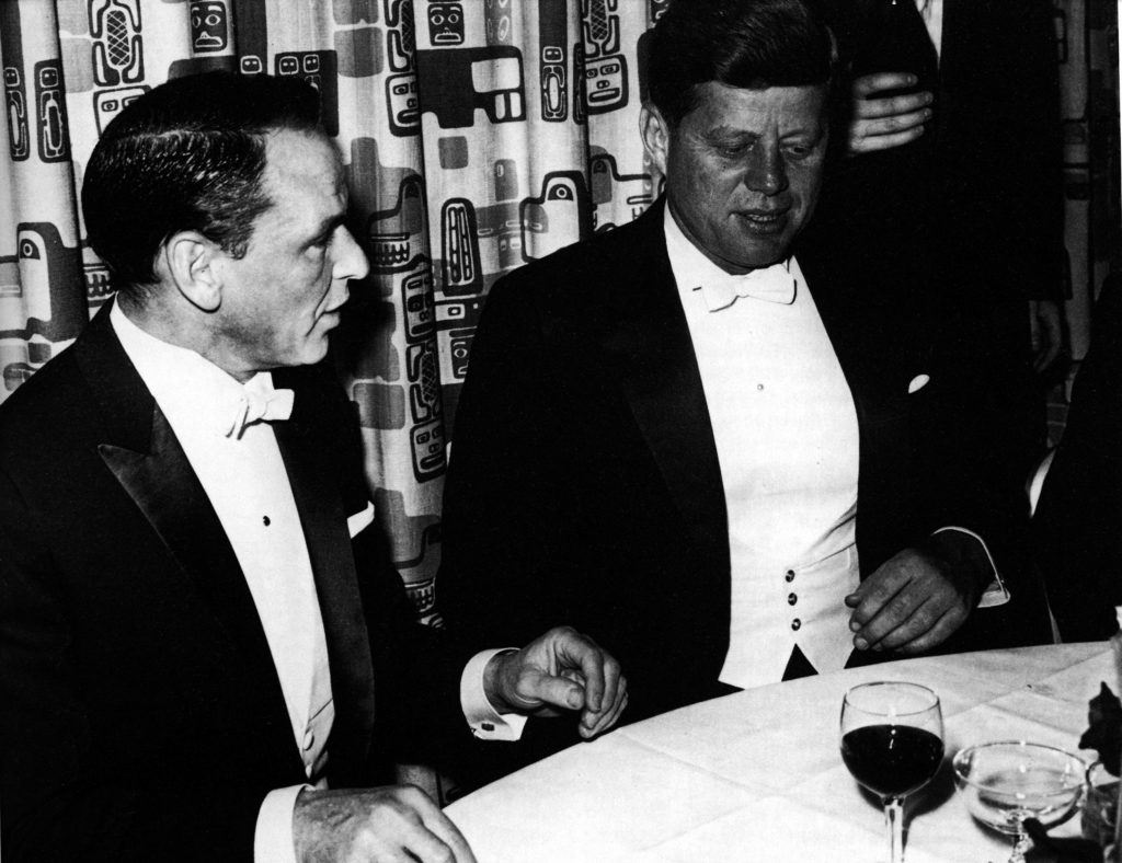 Frank Sinatra and John F. Kennedy sitting at a table together