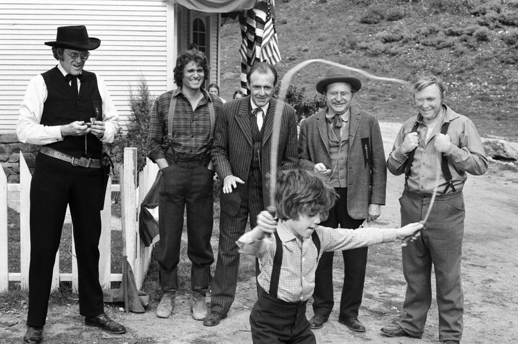 (L-R) Kevin Hagen as Doctor Hiram Baker, Michael Landon as Charles Ingalls, Richard Bull as Nels Oleson, Karl Swenson as Lars Hanson, Wayne Heffley as Mr. Kennedy, Jonathan Gilbert as Willie Oleson (front) | George Hurrell/NBCU Photo Bank