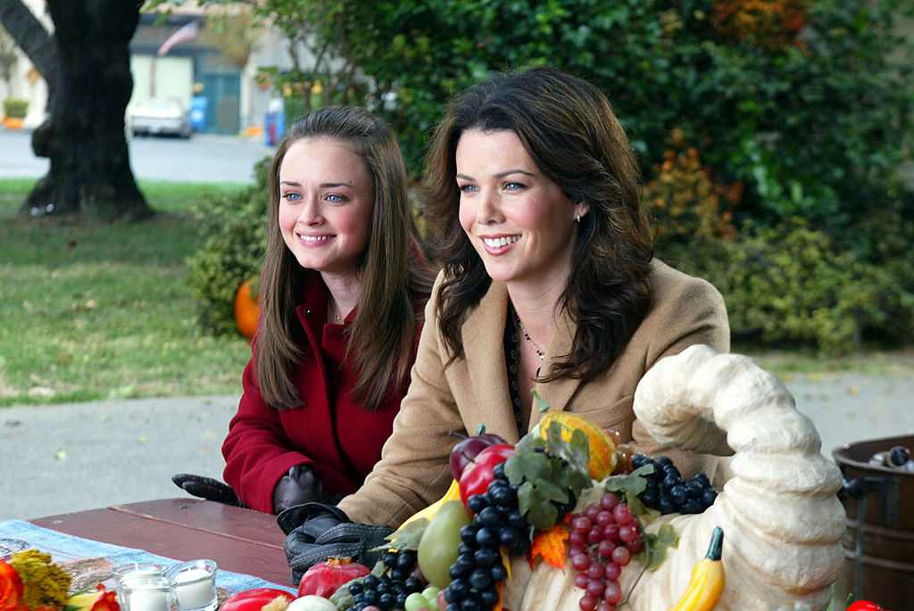 Alexis Bledel and Lauren Graham sit at a table outside on 'Gilmore Girls'