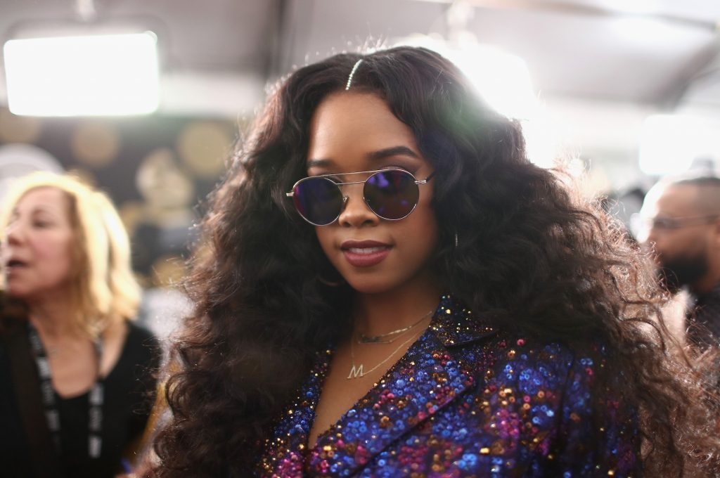 H.E.R. smiling, wearing sunglasses, in front of a blurred crowd