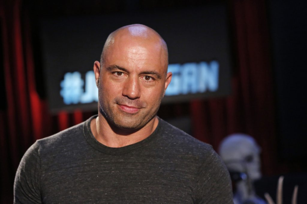 Joe Rogan smiling in front of a blurred background