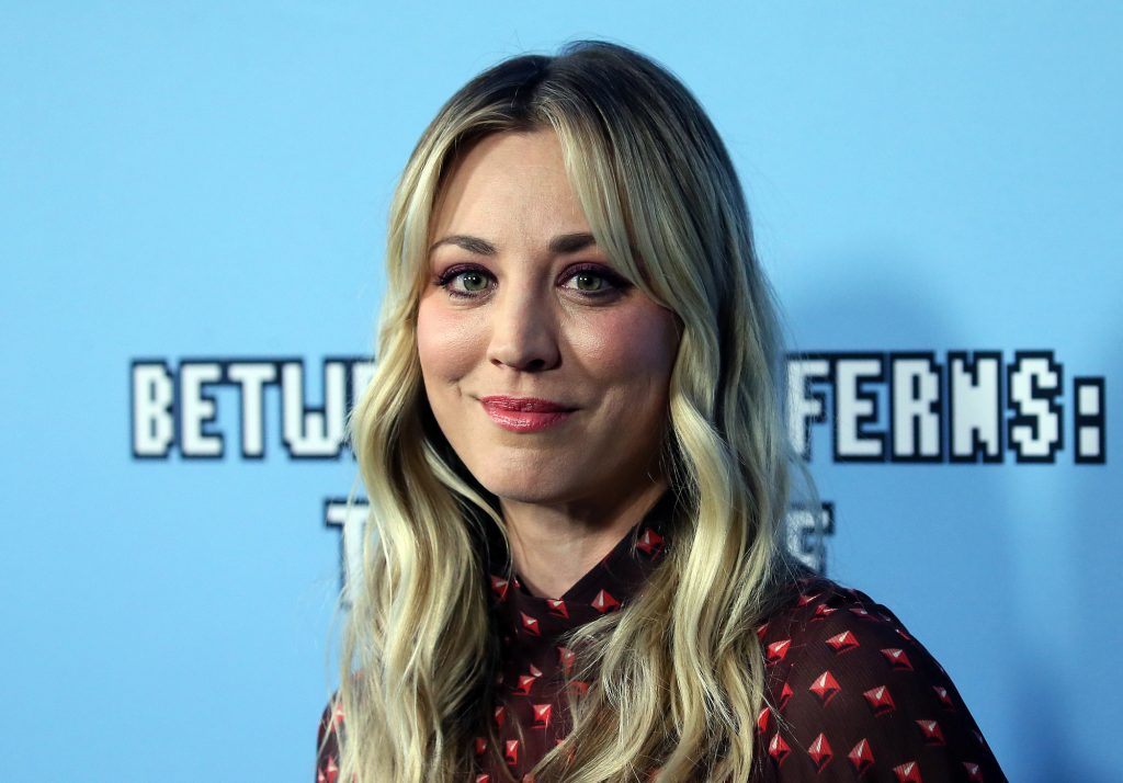 Kaley Cuoco smiling in front of a blue background