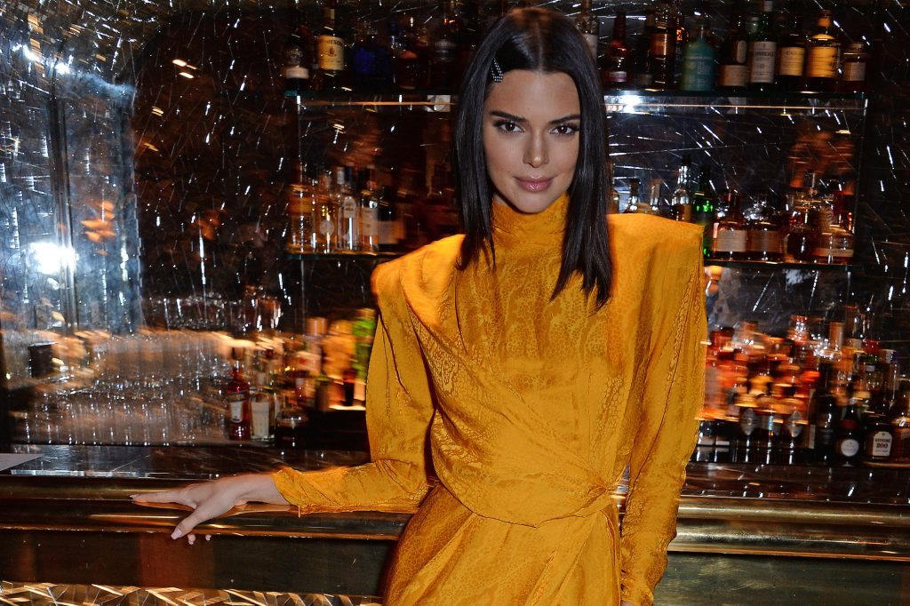 Kendall Jenner smiling in front of a bar