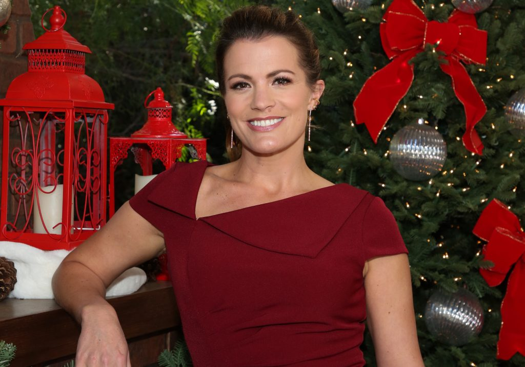 Melissa Claire Egan smiling in front of trees and Christmas decorations
