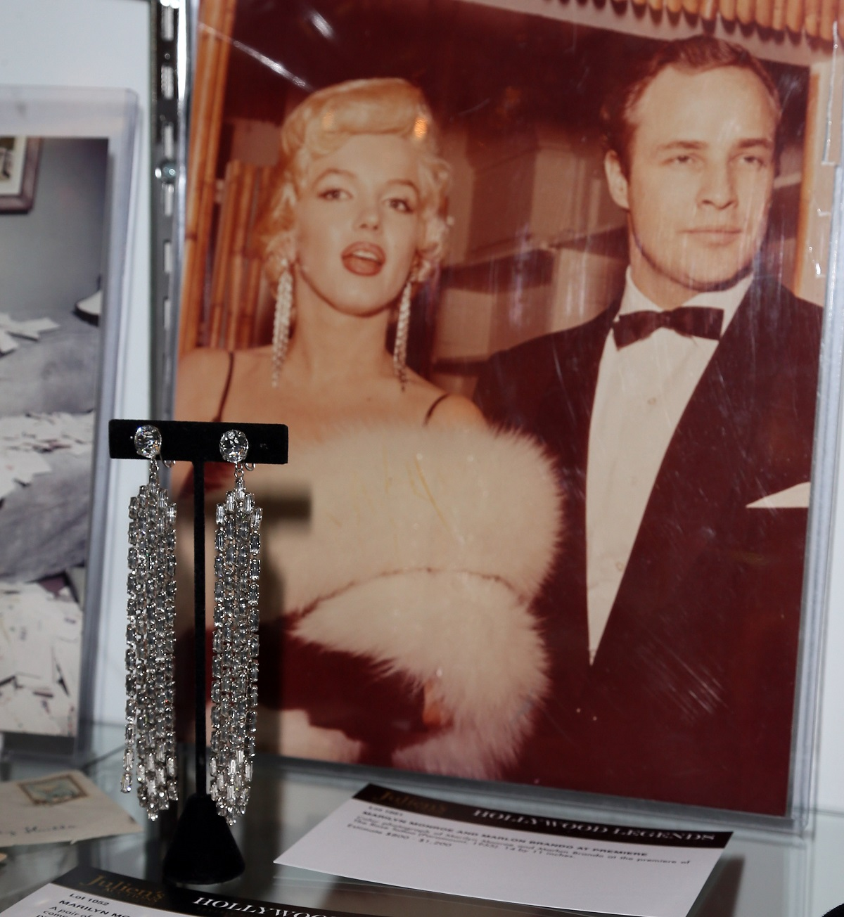 Marilyn Monroe's earrings in front of a photo of Monroe with Marlon Brando at a 2014 auction